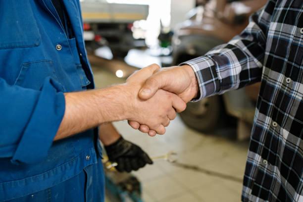 Joven cliente de servicio de reparación y técnico saludarse unos a otros por apretón de manos - foto de stock