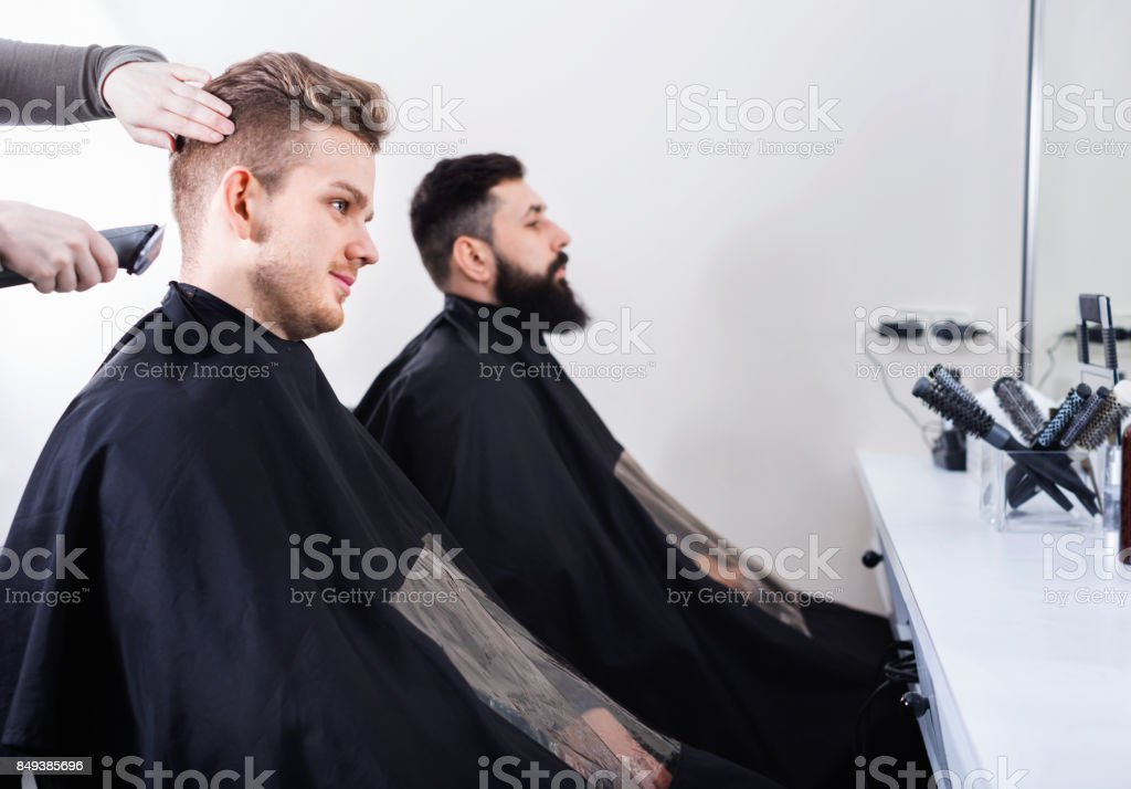 Young clients having their hair cut by hairdressers stock photo