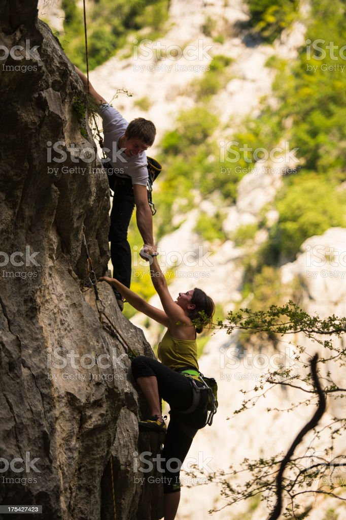 Young climbing couple helping each other in the rock wall stock photo