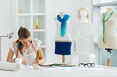 Female fashion designer sitting at the table in clothing design studio and writing.
