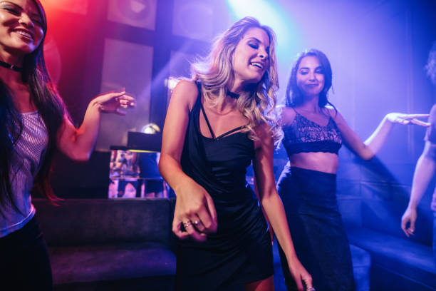 Young clubber dancing surrounded by her friends - foto stock