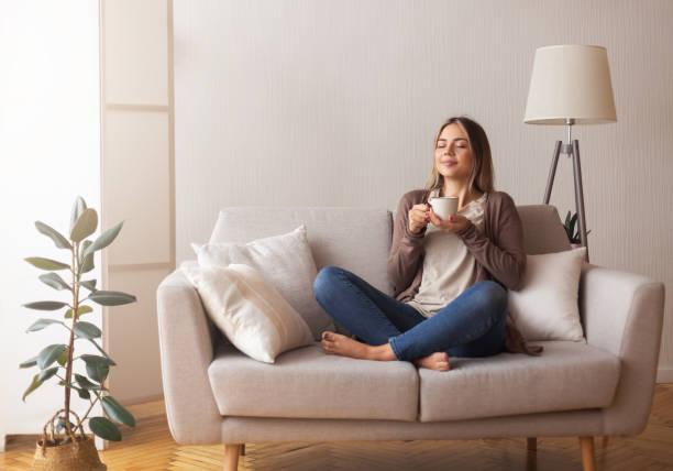 junge kaffee-liebhaber schnüffeln heißes getränk im gemütlichen home interior - entspannung stock-fotos und bilder