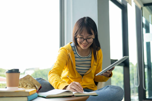 Young collage student using computer and mobile device studying online. stock photo