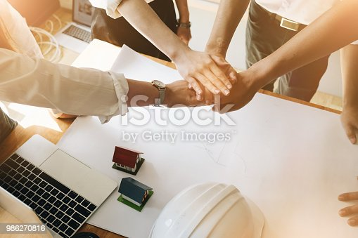 istock Young colleagues joined together their hands, Support together with blueprint of construction project ,small house model and safety helmet in office, Construction Concept. 986270816