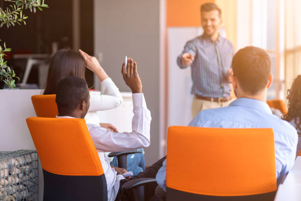 Young colleagues raising hands at the business meeting in office stock photo