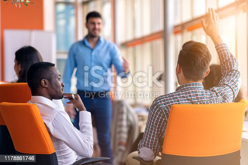 istock Young colleagues raising hands at the business meeting in office 1178861746