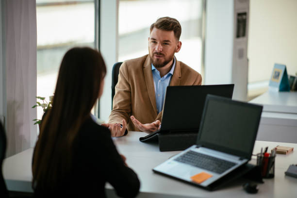 Young colleagues talking to each other in the office stock photo