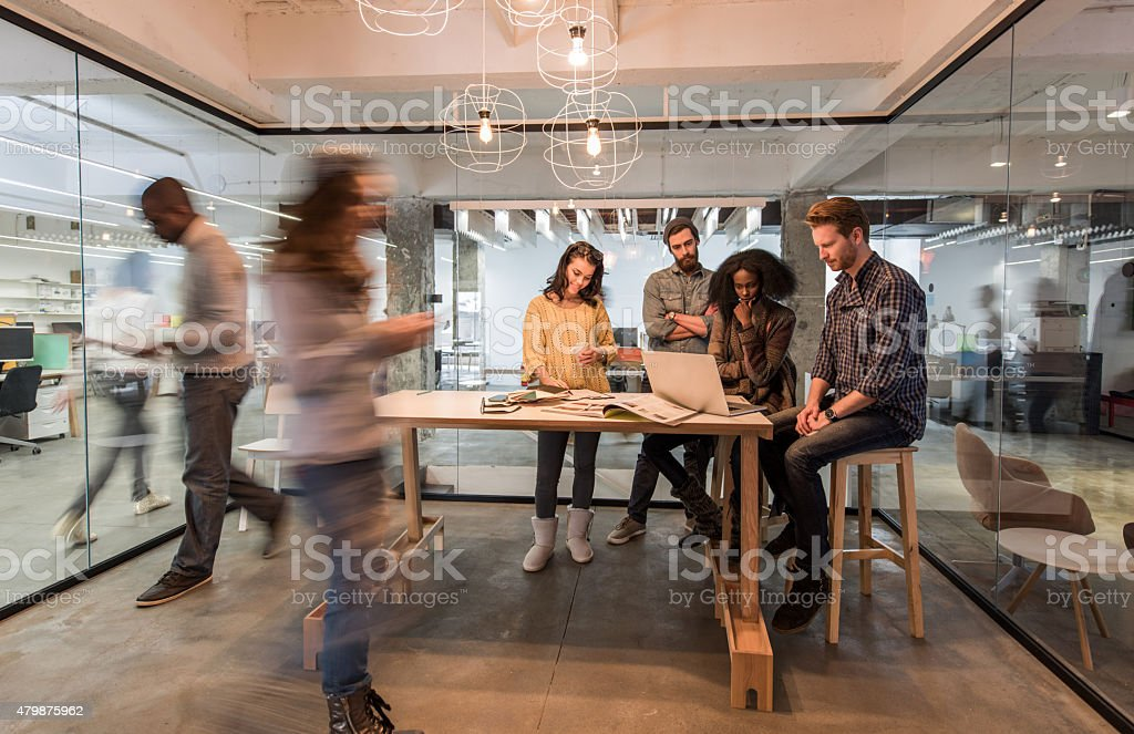 Young colleagues using laptop in the office among blurred people. stock photo
