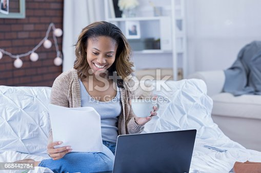 istock Young college student reviews homework assignment 668442784