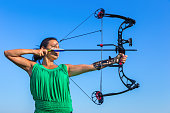 Young black haired colombian woman aiming arrow of compound bow in blue sky. On this sunny day in summer season there was a beautiful blue sky. The female person was training and learning to shoot with bow and arrow.