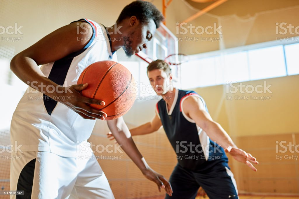 Concentrated sporty young African-American basketball player moving...