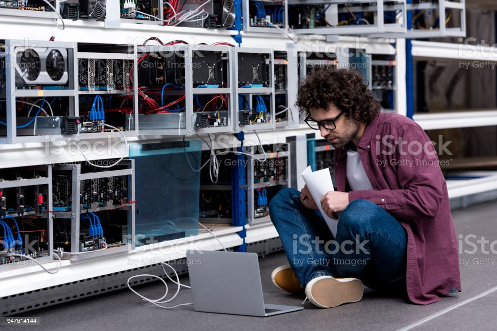 young computer engineer working while sitting on floor at cryptocurrency mining farm royalty-free stock photo