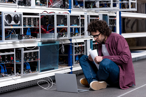 Young Computer Engineer Working While Sitting On Floor At Cryptocurrency Mining Farm Stock Photo - Download Image Now
