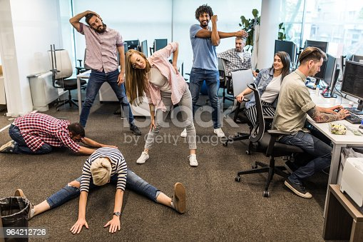 Young computer programmers doing stretching exercises on a break in the office.