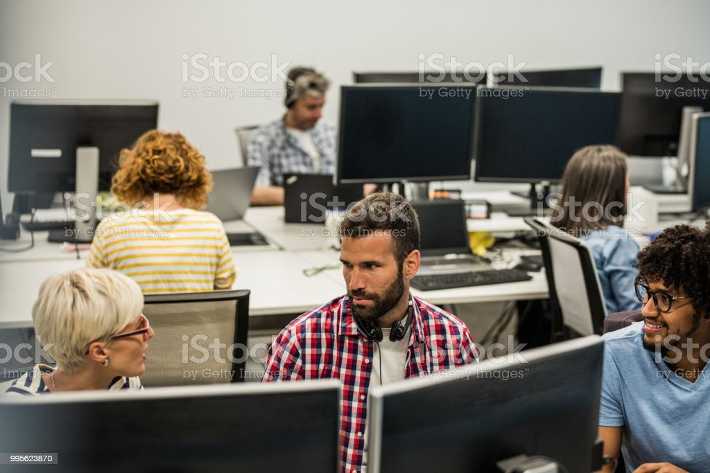 Group of programmers communicating while working on desktop PC in the...