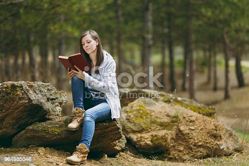 862602714istockphoto Young concentrated beautiful woman in casual clothes sitting on stone studying reading book in city park or forest on green blurred background. Student learning, education. Lifestyle, leisure concept. 964985046