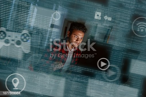 istock Young concentrated indian computer developer writing new code 1077503354