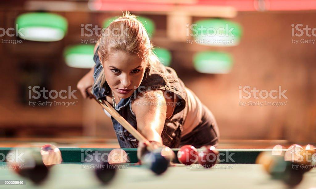 Young beautiful woman playing billiard in a pool hall.