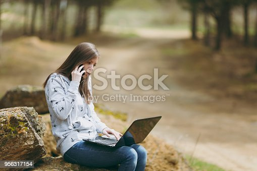 862602714istockphoto Young concerned business woman or student in casual clothes sitting on stone talking on mobile phone in city park or forest using laptop working outdoors on green background. Mobile Office concept. 956317154