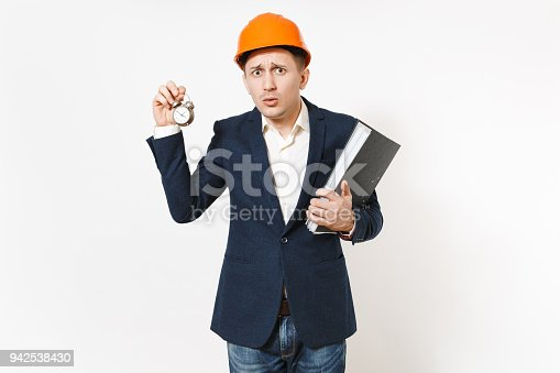 istock Young concerned businessman in dark suit, protective hardhat holding black folder for papers document and alarm clock isolated on white background. Time is running out. Male worker for advertisement. 942538430