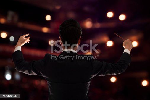 Young conductor with baton raised at a performance, rear view