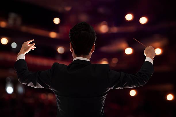 Junge Dirigent mit baton hoch in einem performance, Rückansicht – Foto