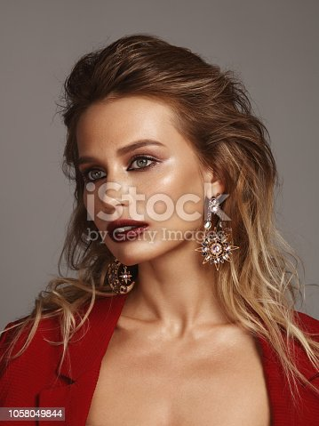 Portrait of beautiful young woman wearing red blazer and statement earrings