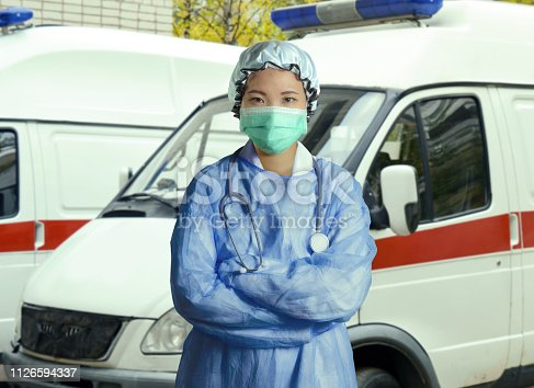 istock young confident and successful Asian Korean medicine doctor woman in hospital scrubs and mask posing outdoors with ER ambulance background in medical health care as emergency physician 1126594337