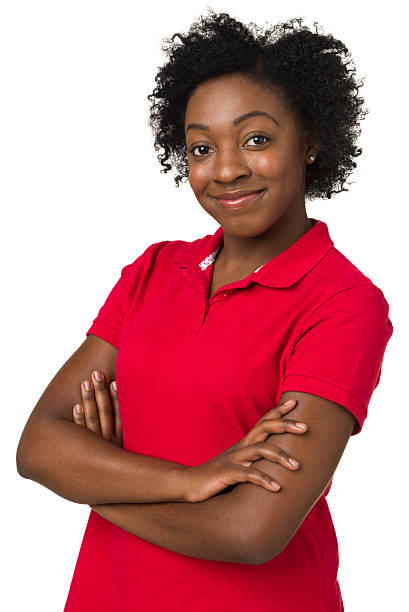 Young, confident black woman in red shirt with arms crossed Portrait of a young woman on a white background. red shirt stock pictures, royalty-free photos & images