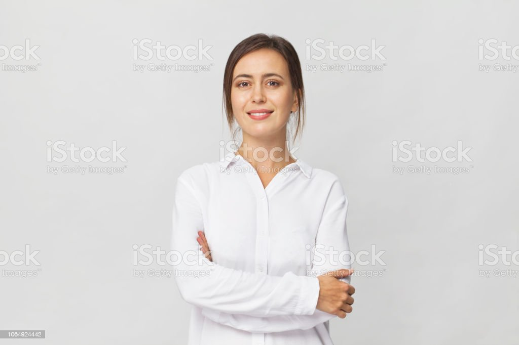 Young confident brunette woman in white elegant shirt smiling portrait against white background royalty-free stock photo