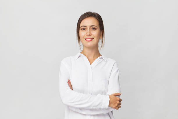 young confident brunette woman in white elegant shirt smiling portrait against white background - portrait стоковые фото и изображения