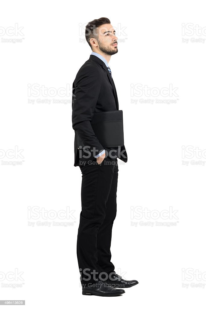 335c838d9 Young confident businessman holding documents folder looking away side view  - Stock image .