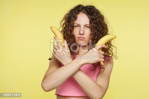 istock Young confident cool female plays at cowboy, makes guns from bananas. Good looking woman pretends to make gun shoot , gestures with hands and blows lips, looks at camera. Self assurance concept. 1020111972