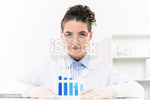 1147277006 istock photo Young confident female laboratory worker in protective eyeglasses and gloves 1200366323