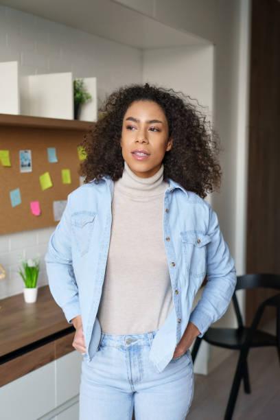 ホームオフィスのインテリアに立っている若い自信のあるgen zアフリカの十代の女の子。屋内を見渡すミレニアル世代の混血女性。アフロアメリカの十代の大学生、フリーランサーの女性垂� - gen z ストックフォトと画像