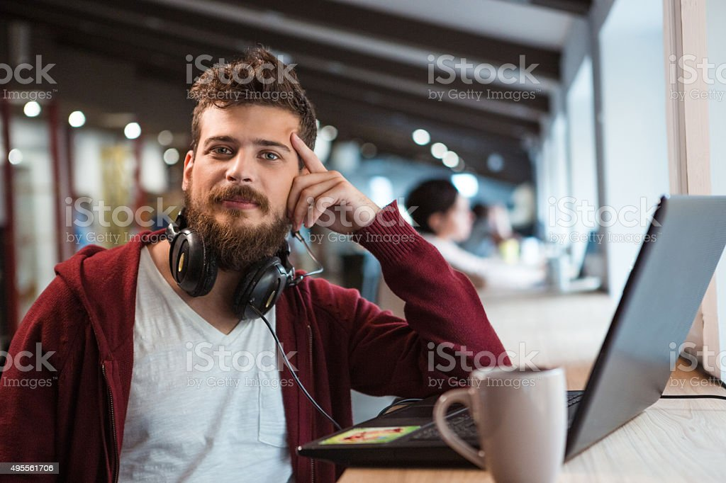 Young confident guy working in office using headset and laptop stock photo