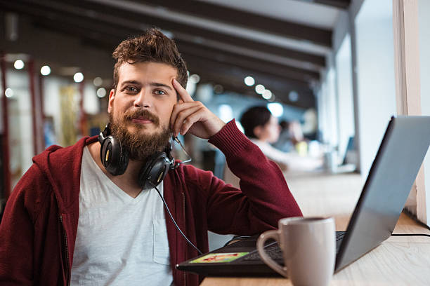 Young confident guy working in office using headset and laptop Young handsome confident guy in brown hoodie working in office using headset and laptop nerd stock pictures, royalty-free photos & images