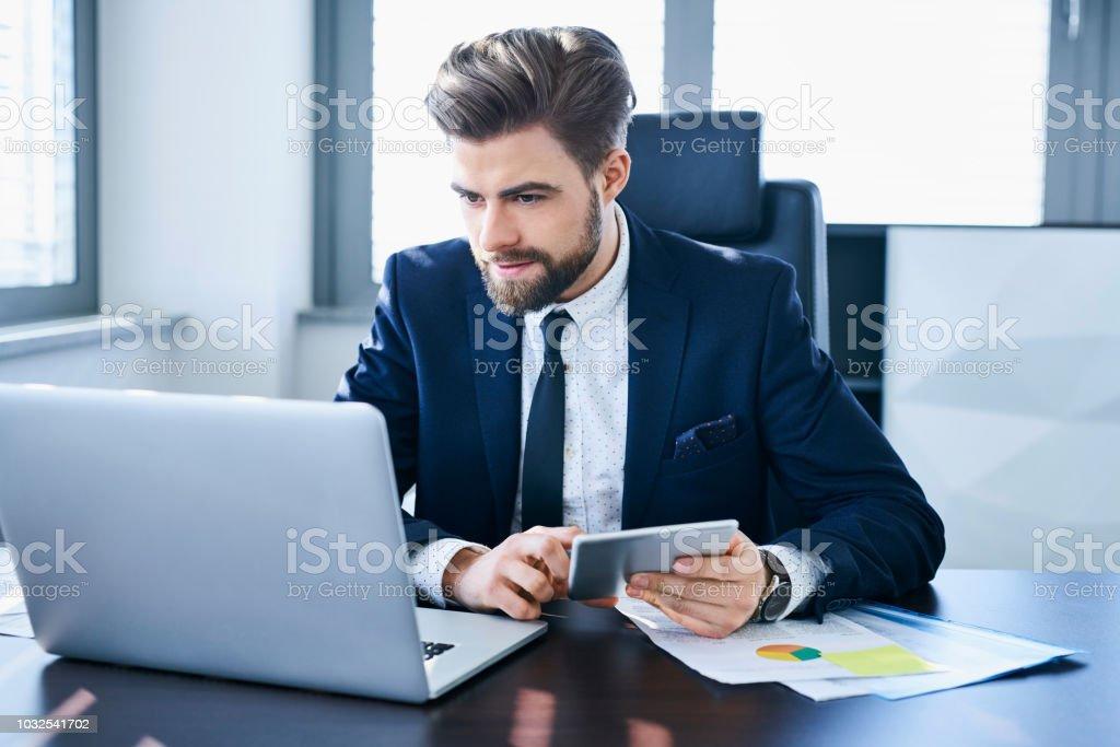 Employé de jeune bureau confiant à laide de tablette et ordinateur