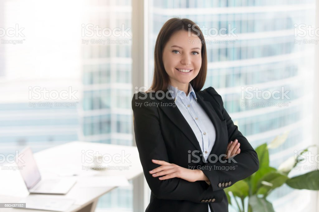 Young confident smiling businesswoman standing in office with arms crossed stock photo