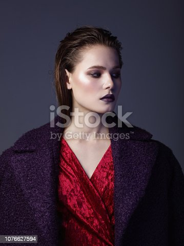 Portrait of beautiful young woman wearing purple coat and red velvet dress