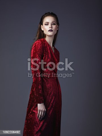 Portrait of beautiful young woman wearing red velvet dress
