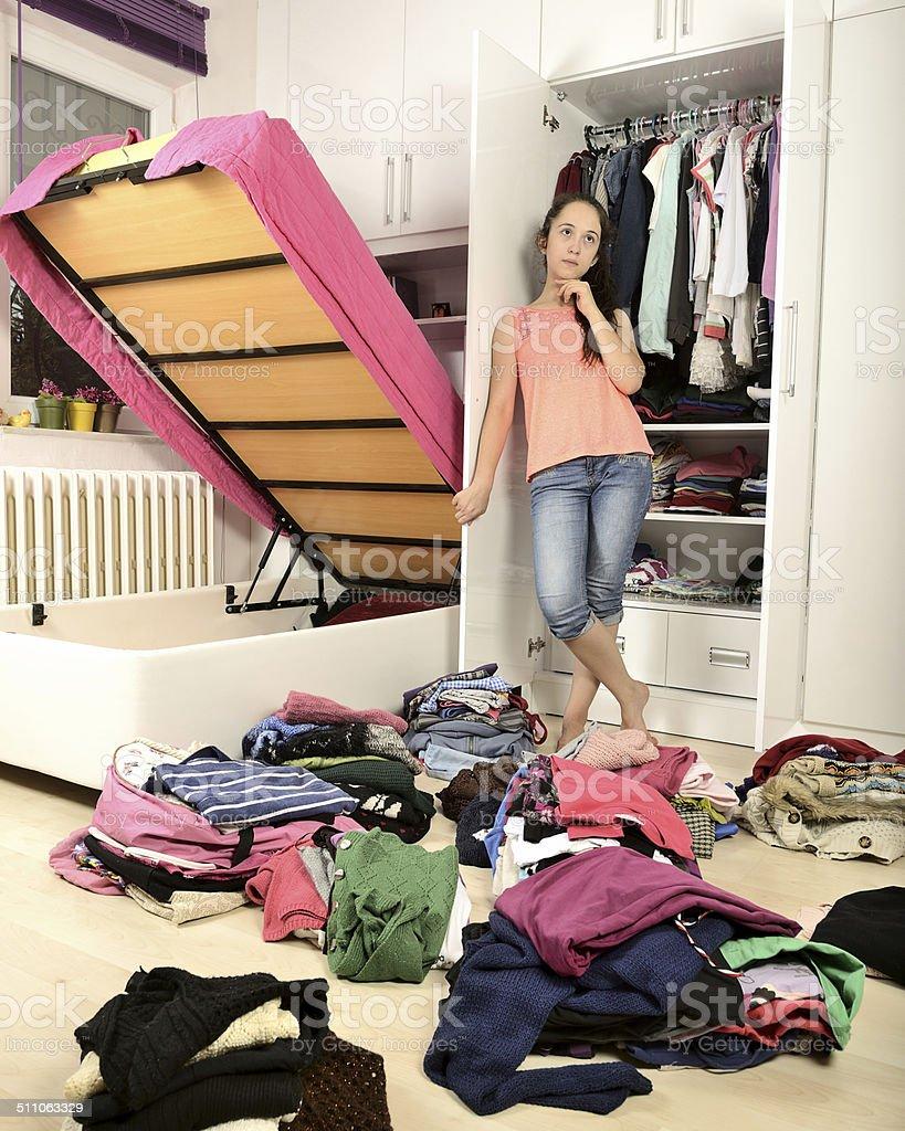 Young confuso girl standing in front of un vestidor - foto de stock