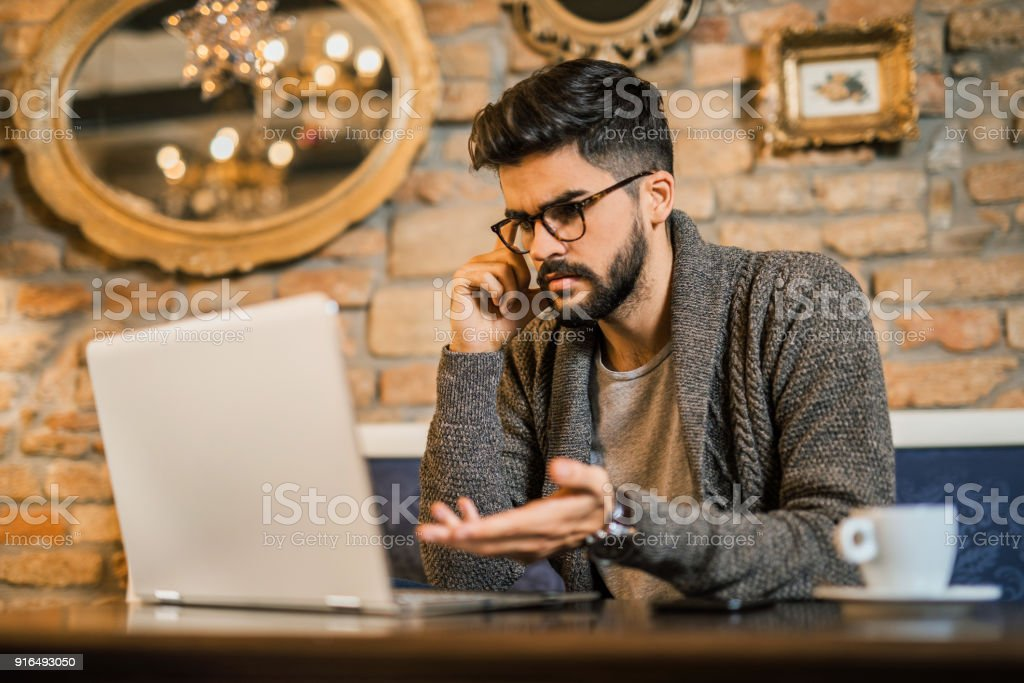 Young confused man looking at his laptop . stock photo