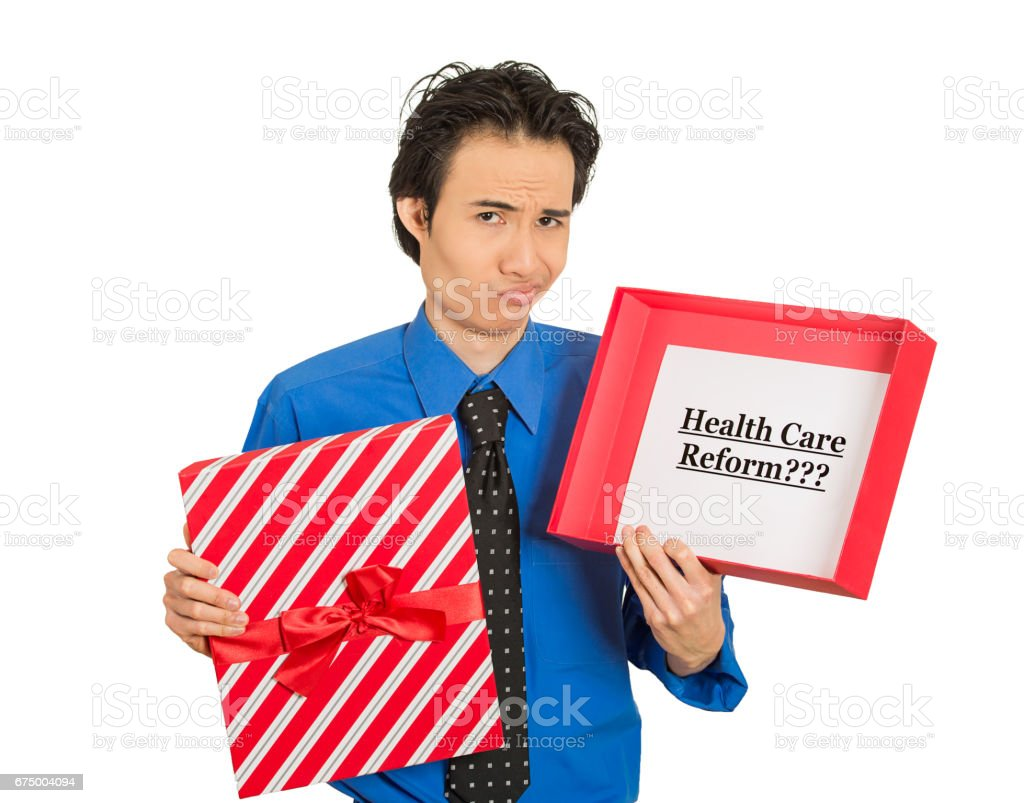 young confused skeptical man holding sign health care reform in gift box, uncertain of universal insurance coverage stock photo