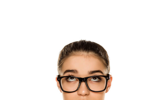 Young confused woman with glasses looking up on white background stock photo