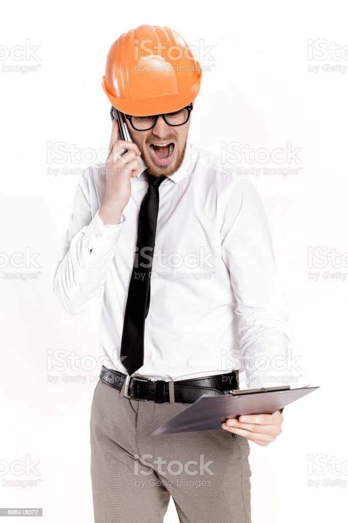Young construction engineer in orange helmet with folder talking on phone on white background stock photo