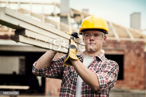 istock Young construction worker carrying wood boards 163204230