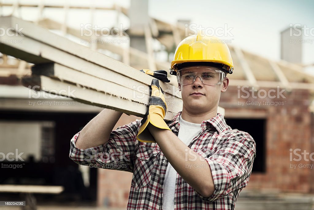 Young construction worker carrying wood boards stock photo