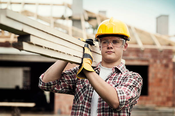 young construction worker carrying wood boards - builders stock photos and pictures