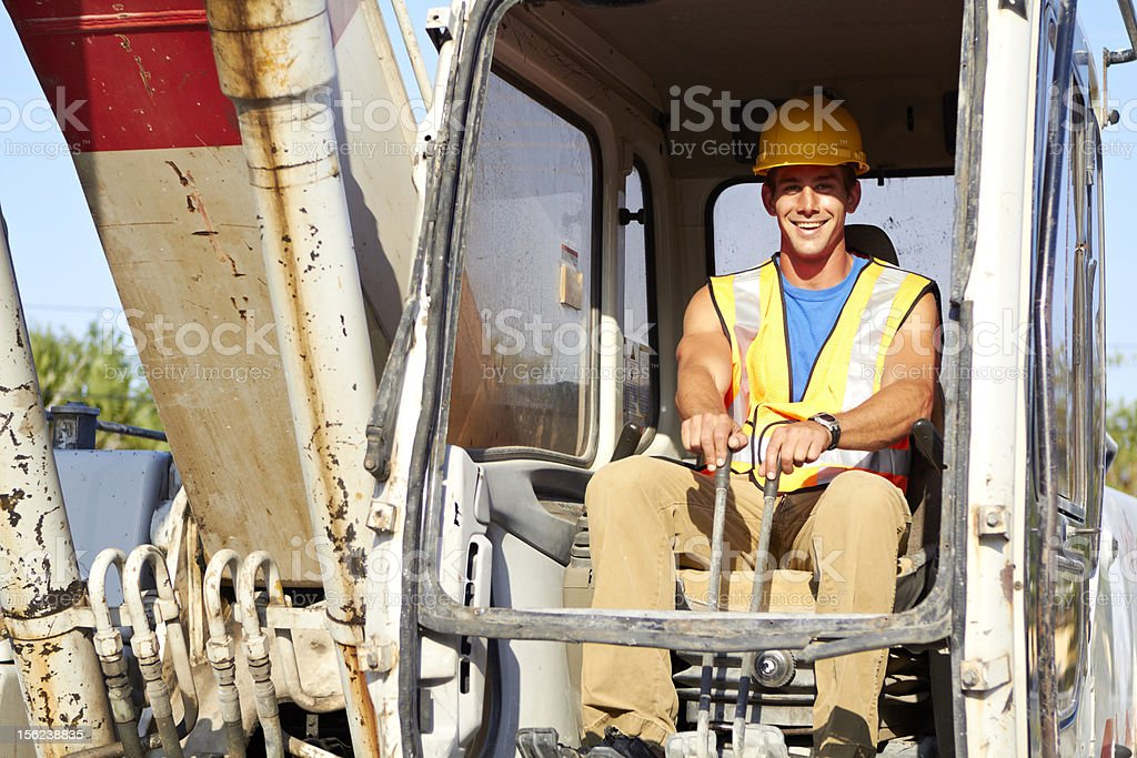 Young construction worker driving forklift royalty-free stock photo